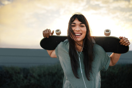 Woman with skateboard outdoors