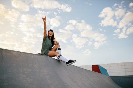 Woman sitting on skateboard ramp at skate park