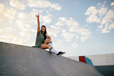 Woman sitting on skateboard ramp at skate park