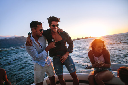 Friends enjoying in a sunset boat party
