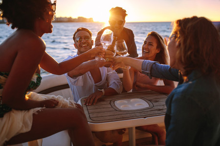 Group of friends having drinks at sunset boat party