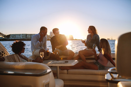 Group of friends partying on yacht at sunset