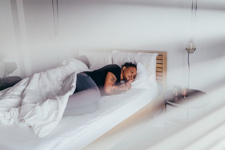 African man sleeping in bedroom with woman