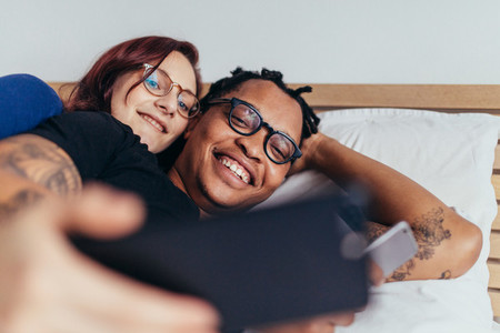 Multiracial couple taking selfie in bed