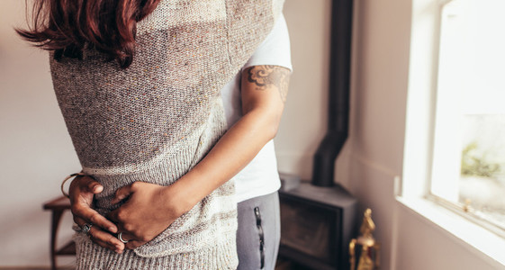 Close of couple embracing at home
