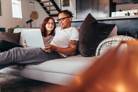 Couple relaxing on sofa at home with laptop
