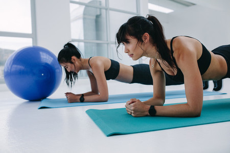Two fit women doing planks exercise at gym