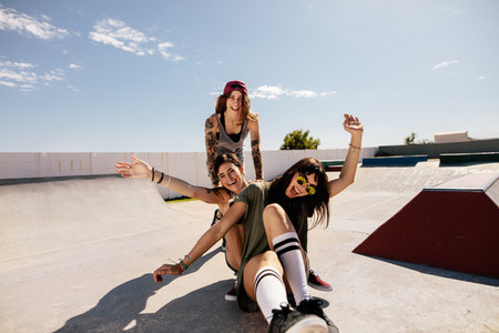 Female friends having fun with skateboard in the skate park