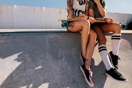 Female skaters sitting together on skating ramp