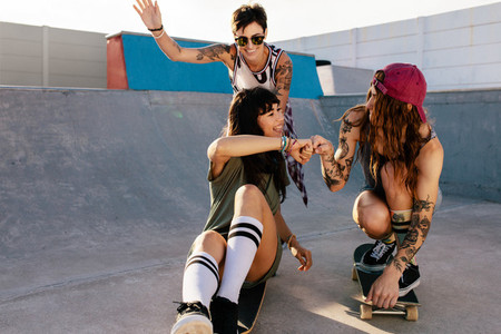 Female friends playing with skateboard at skate park