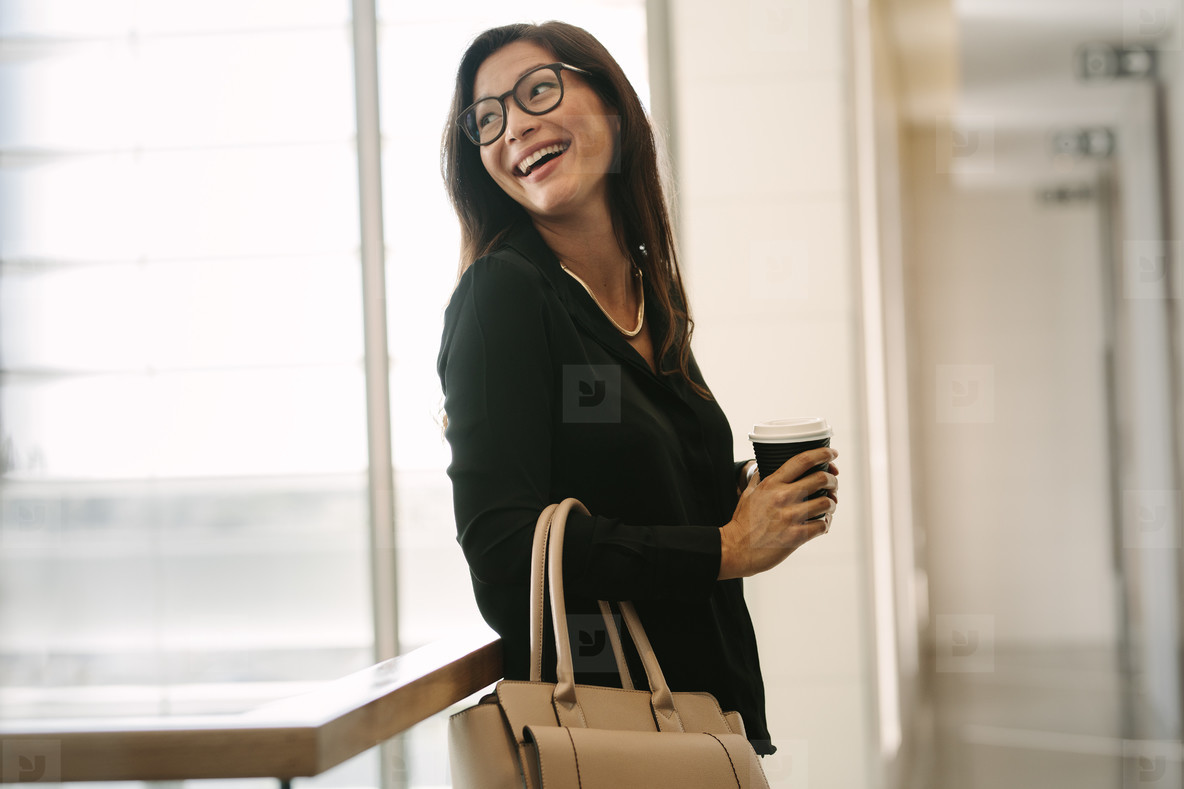 Female executive standing in office during break
