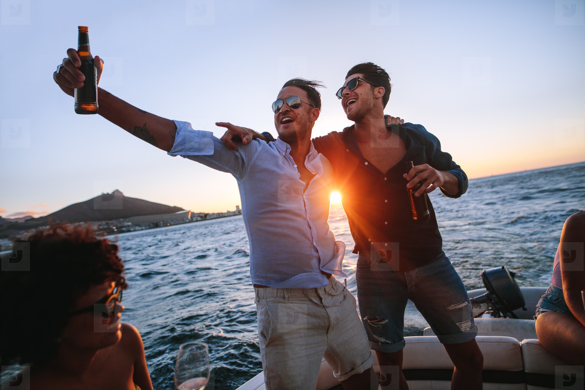 Men having a great time at evening boat party