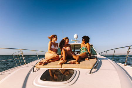 Three girls hanging out on a private yacht deck