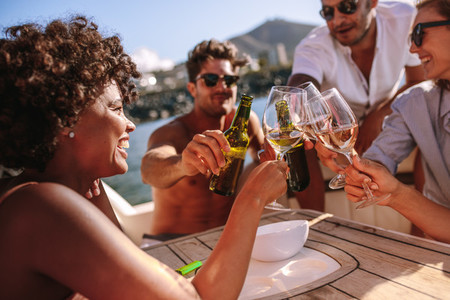 Group of people toasting drinks at boat party