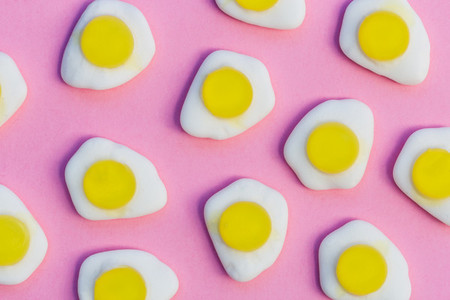 Fried eggs candy sweets on pink background