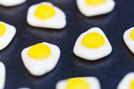 Fried eggs candy sweets on dark background