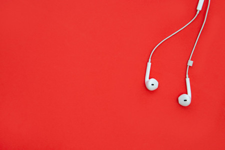White music earphones isolated on red background