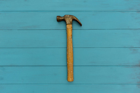 Old hammer on wood texture background