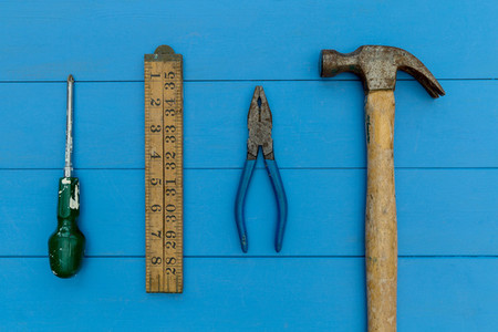 Old hammer and DIY tools on wood background