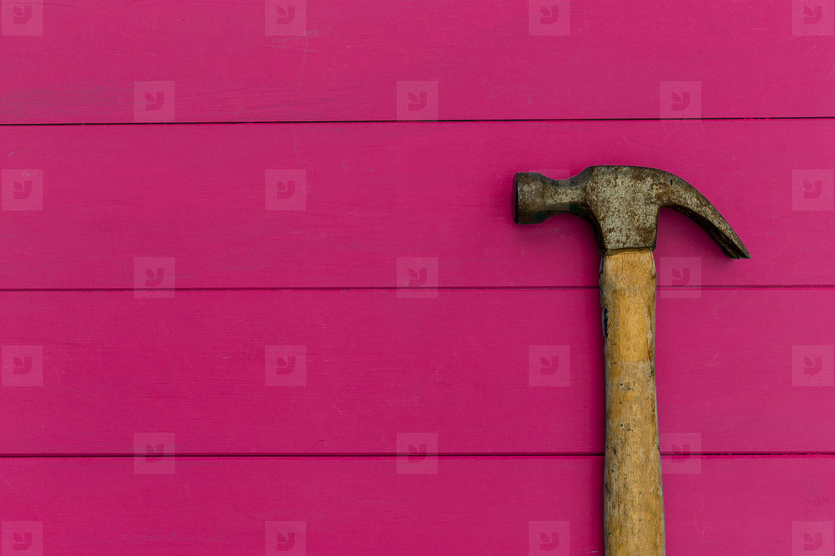 Old hammer on pink wood texture background