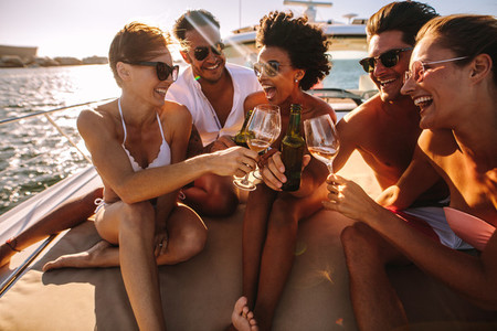 Multiracial friends toasting drinks on the yacht deck
