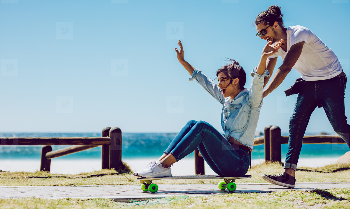 Loving couple playing on skateboard near the beach