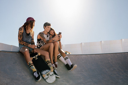 Female skaters using smart phone at skate park
