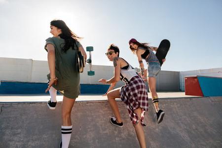 Happy female friends running over skateboard ramp