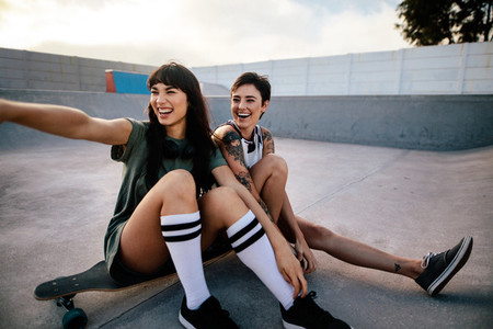 Smiling female skaters hanging out at skate park