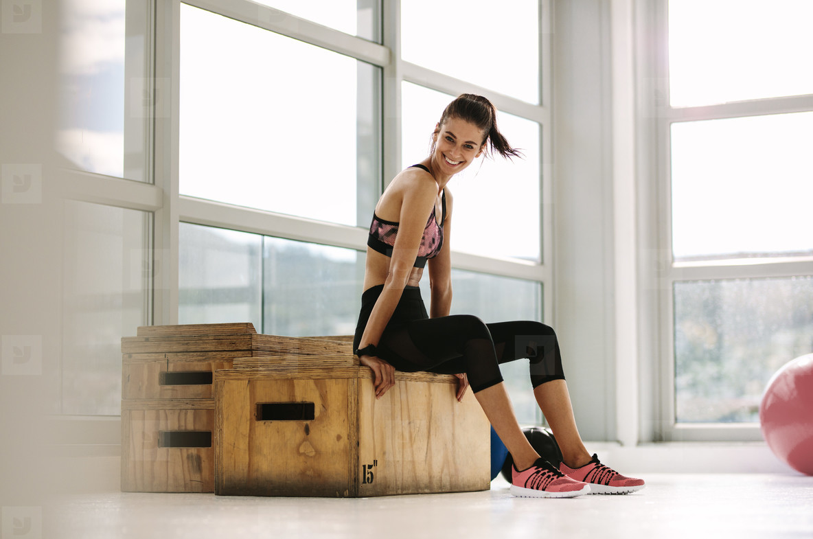 Smiling female athlete resting at gym