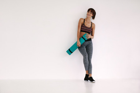 Smiling woman with yoga mat in studio
