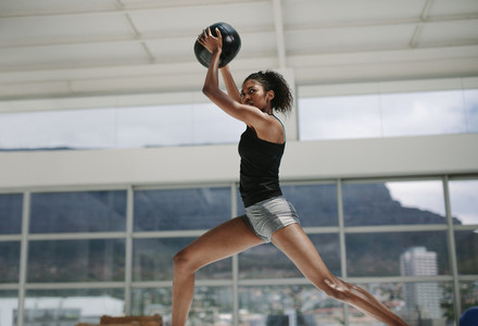 Sportswoman doing exercise with fitness ball
