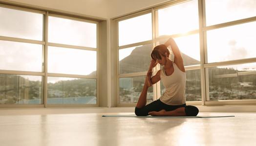 Woman doing yoga at fitness studio