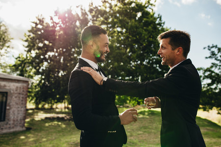 Groom talking with his best man at wedding party