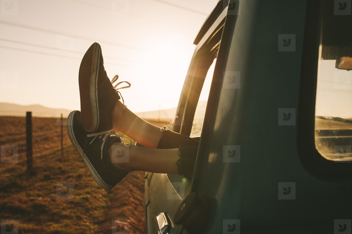 Close up of legs hanging out of a car on highway