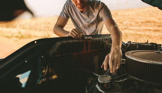 Man repairing his car on highway