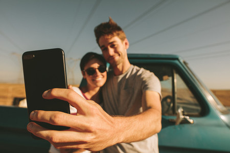 Couple on a road trip taking selfie