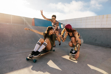 Female friends enjoying skateboarding at skate park