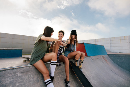Three women hanging out at skate park
