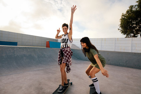 Female friends skateboarding together at skate park