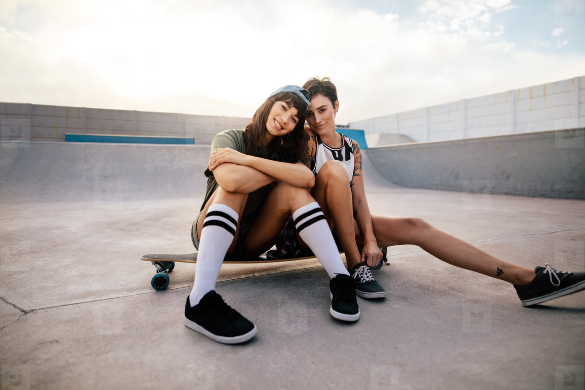 Female skateboarders hanging out at skate park