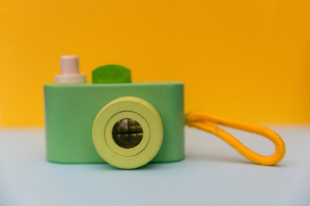 Cute green retro camera on yellow background