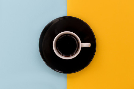 Coffee cup  saucer on yellow and blue background