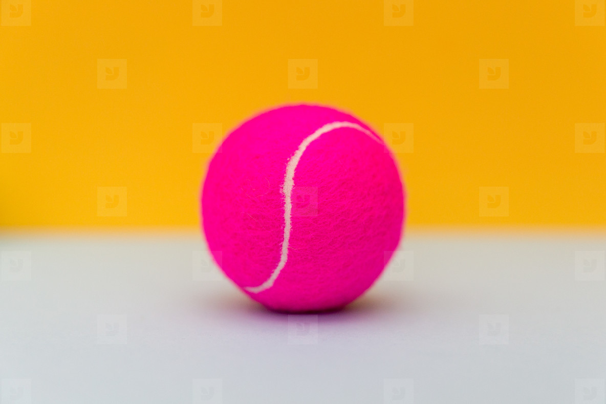 Pink tennis ball on yellow background
