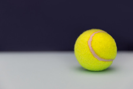 Yellow tennis ball on dark background