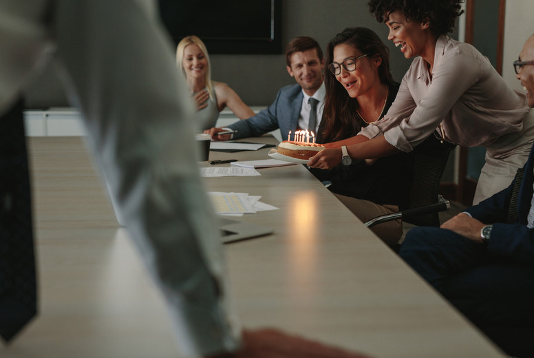Coworkers celebrating birthday of a female colleague in office