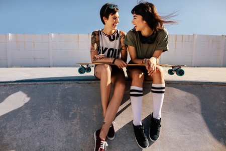 Female friends in skate park laughing and having fun