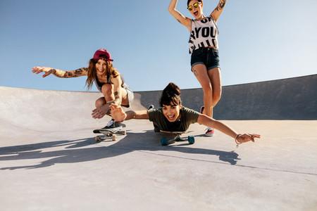Women riding skateboards and having fun at skate park