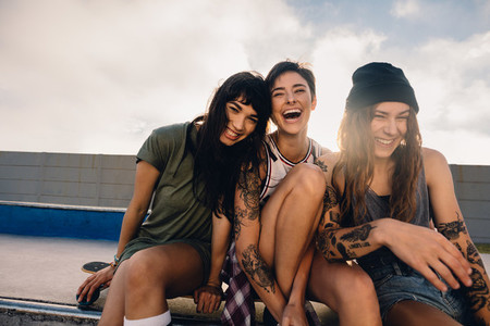 Three smiling girls hanging out at skate park