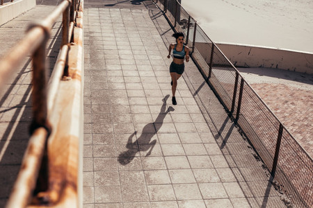 Female athlete running on seaside boardwalk